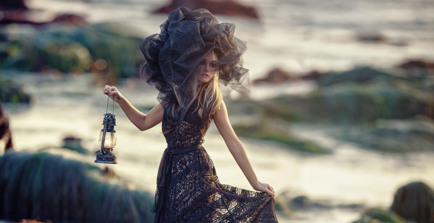 Fashion Photography of a Sea Goddess holding a lantern on a rocky beach